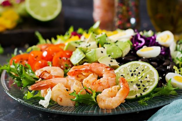 ヘルシーなサラダプレート。新鮮なシーフードのレシピ。エビのグリルと新鮮野菜のサラダ-アボカド、トマト、黒豆、赤キャベツ、パプリカ。海老のグリル。健康食品。