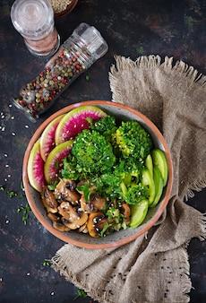 ビーガンブッダボウルディナーフードテーブル。健康食品。健康的なビーガンランチボウル。キノコのグリル、ブロッコリー、大根のサラダ。平干し。上面図。