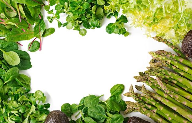 Зеленые травы, спаржа и черный авокадо на белом фоне. вид сверху. плоская планировка