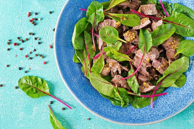 Салат из куриной печени и листьев шпината и мангольда. плоская планировка вид сверху