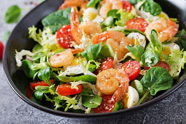 ヘルシーなサラダプレート。新鮮なシーフードのレシピ。エビのグリルと新鮮野菜のサラダと卵。海老のグリル。健康食品。