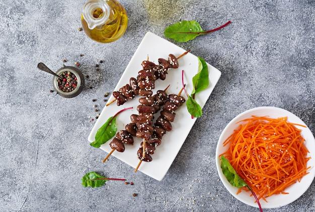 Куриные сердечки в остром соусе и салат из моркови. здоровая пища. вид сверху