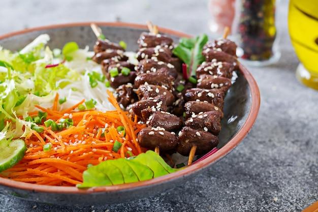 Куриные сердечки в остром соусе с лапшой и овощным салатом. здоровая пища.