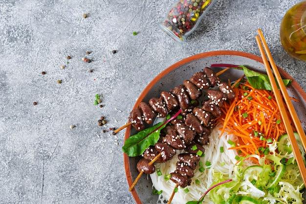 Куриные сердечки в остром соусе с лапшой и овощным салатом. здоровая пища. вид сверху