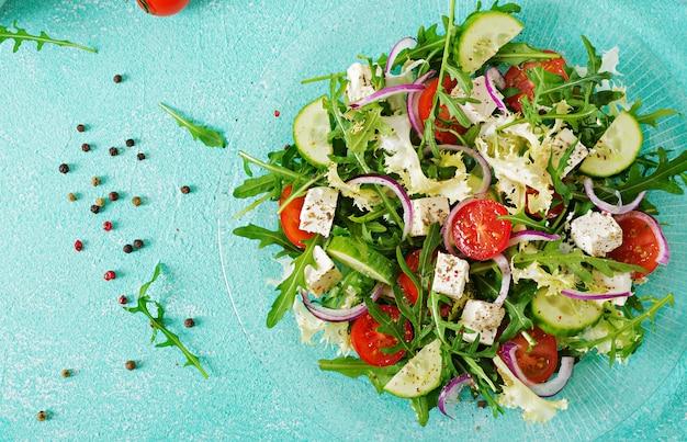 新鮮な野菜のサラダ-ギリシャ風のトマト、キュウリ、フェタチーズ。平干し。上面図