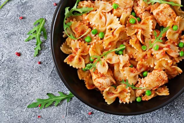 Паста фарфалле с куриным филе, томатным соусом и зеленым горошком. итальянская кухня. меню еды. вид сверху. ужин.
