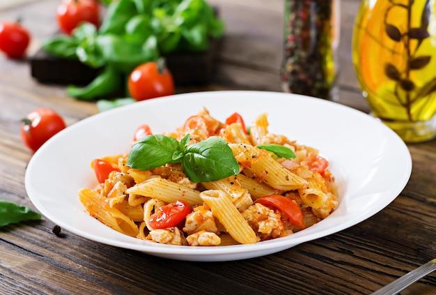木製テーブルの上のバジルで飾られた鶏肉、トマト、トマトソースのペンネパスタ。イタリア料理。ボロネーゼパスタ。