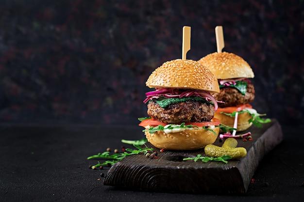 Большой бутерброд - гамбургер с говядиной, помидорами, базиликом и рукколой.