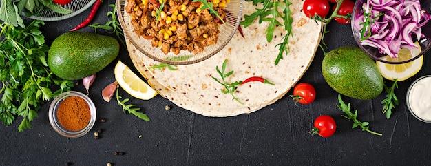 ブリトーの材料は、牛肉と野菜を黒で包みます。メキシコ料理。上面図。平置き