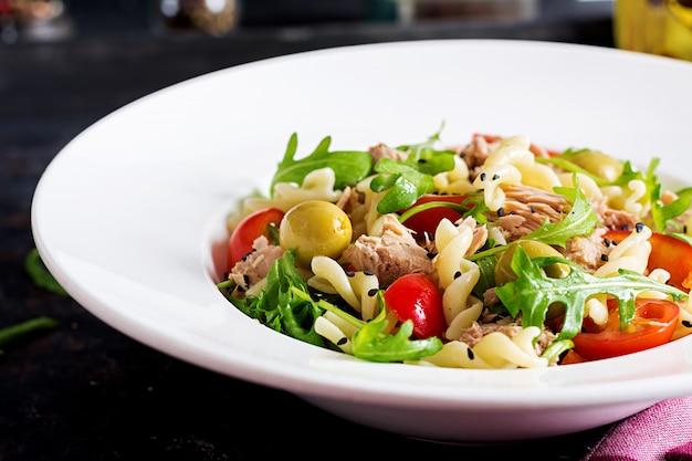 Салат из макарон с тунцом, помидорами, оливками, огурцом, сладким перцем и рукколой на деревенском фоне.