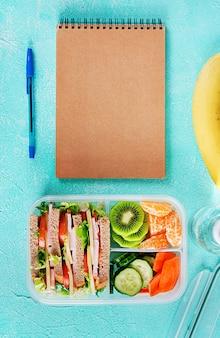 サンドイッチ、野菜、水、果物をテーブルに置いた給食ボックス。