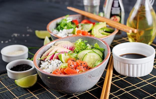 Рыба гавайского лосося тушится с рисом, огурцом, редисом, кунжутом и лаймом.