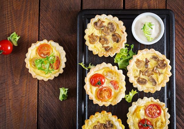 キノコ、チェダー、木製のテーブルにトマトのタルト。
