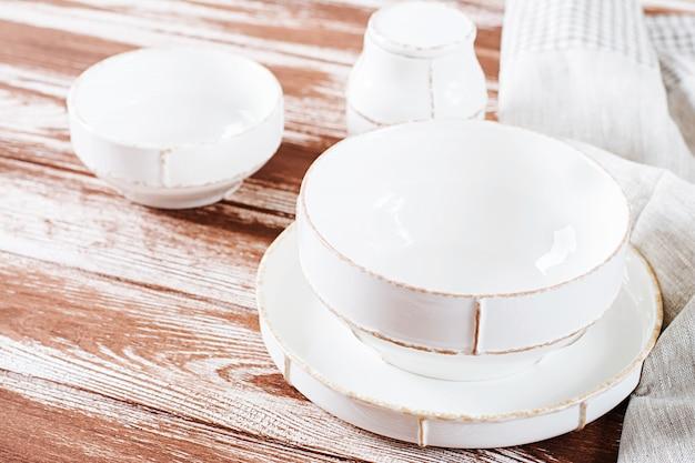 Белая тарелка и миска на деревянном столе