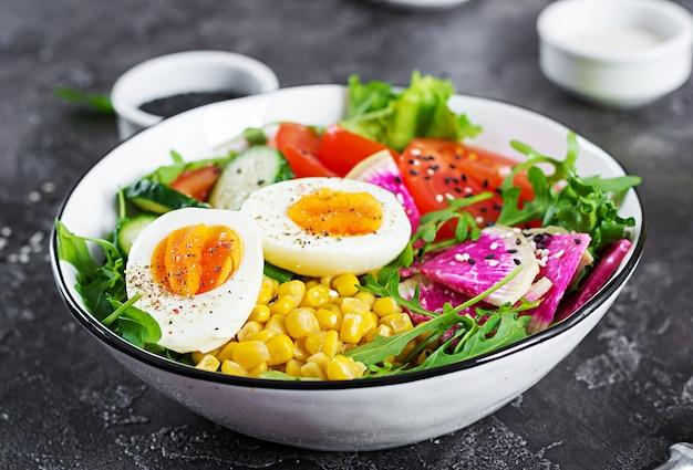 Свежий салат. чаша со свежими сырыми овощами - огурцом, помидором, арбузной редькой, салатом, рукколой, кукурузой и вареным яйцом. здоровая пища. вегетарианская чаша будды.