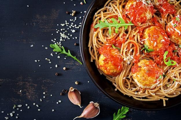 イタリアのパスタ。ミートボールと暗い素朴な木製の背景に黒のプレートでパルメザンチーズのスパゲッティ。晩ごはん。上面図。スローフードのコンセプト