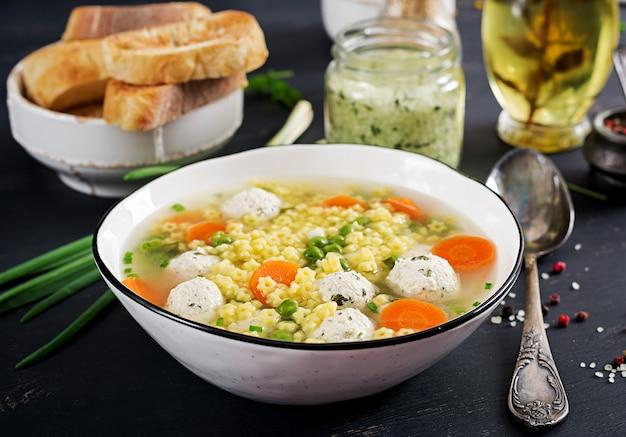 黒いテーブルの上のボウルにイタリアのミートボールスープとステリーングルテンフリーパスタ。栄養スープ。ベビーメニュー。おいしい食べ物。