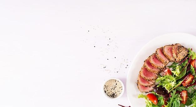 日本の伝統的なサラダ、ミディアムレアのマグロとゴマのグリル、新鮮な野菜サラダのプレート添え