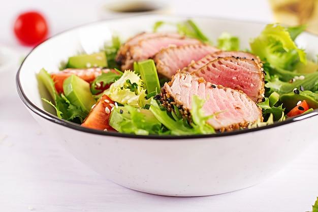ミディアムレアのマグロとゴマのグリルと新鮮な野菜をボウルに乗せた日本の伝統的なサラダ。
