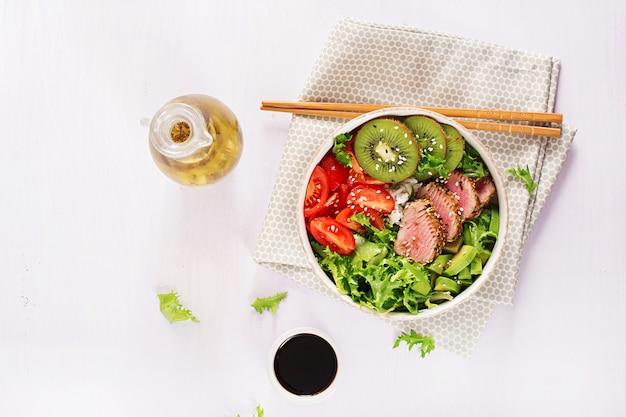 ミディアムレアのアヒマグロとゴマのグリルと新鮮な野菜サラダと皿にご飯を添えた伝統的なサラダ。