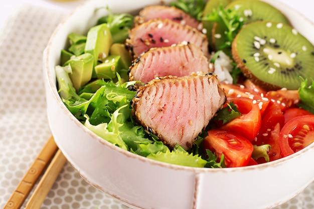 ミディアムレアのアヒマグロとゴマを新鮮な野菜とご飯の上に乗せたプレートの伝統的なサラダ。