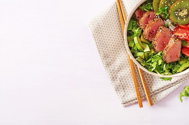 Традиционный салат с кусочками средне-редкого жареного тунца ахи и кунжута со свежими овощами и рисом на тарелке.