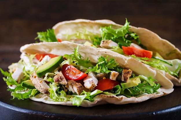 木製の背景に鶏肉のグリル、アボカド、トマト、キュウリ、レタスのピタパンサンドイッチを提供しています。