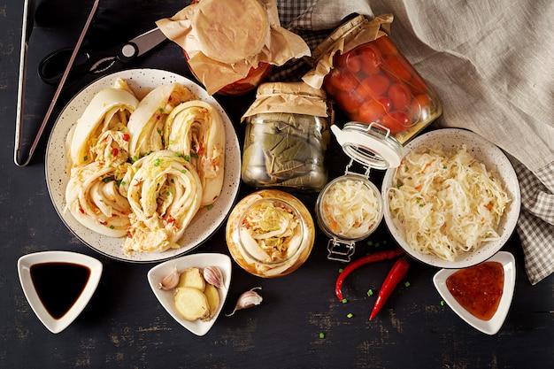 Капуста кимчи, помидоры маринованные, квашеная капуста кислые стеклянные банки на деревенском кухонном столе.