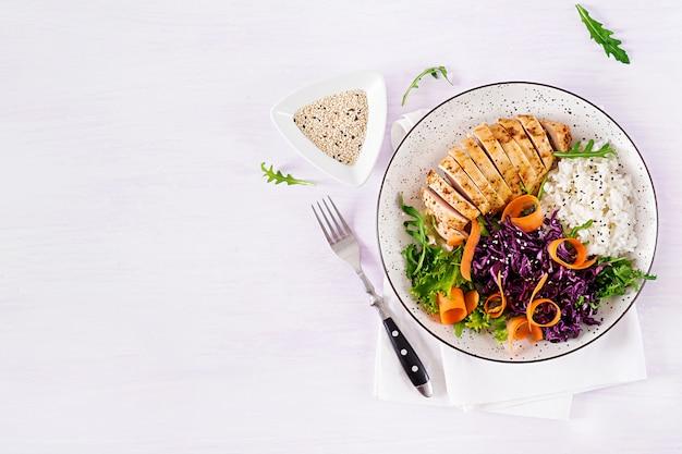 Блюдо «чаша будды» с куриным филе, рисом, красной капустой, морковью, салатом из свежих листьев салата и кунжутом.