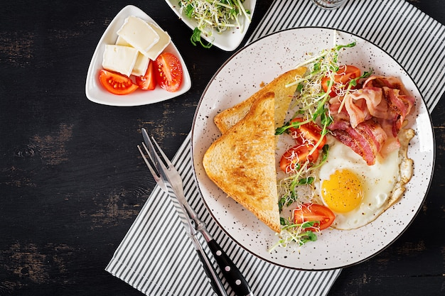 トースト、卵、ベーコン、トマト、マイクログリーンのサラダ。