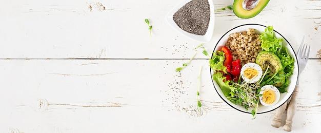 Чаша для завтрака с овсяной мукой, паприкой, авокадо, салатом, микрогринами и вареным яйцом.