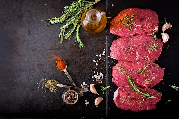 生の牛肉ステーキとスパイスとローズマリー。フラットレイアウト。トップビュー