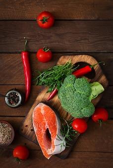 生ステーキサーモンと素朴なスタイルの木製テーブルで調理するための野菜。上面図