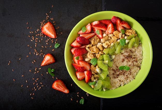 ベリー、ナッツ、亜麻の種子が入ったおいしいヘルシーなオートミールポリッジ。健康的な朝食。フィットネス食品。適切な栄養。平干し。上面図