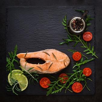 黒いテーブルで野菜とスチームサーモンステーキで調理。上面図