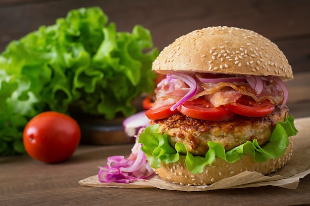 大きなサンドイッチ-牛肉、赤玉ねぎ、トマト、揚げベーコンのハンバーガーバーガー。