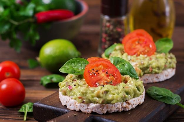 健康的な朝食。ワカモレと木製のテーブルの上のトマトのぱりっとしたパンのサンドイッチ。