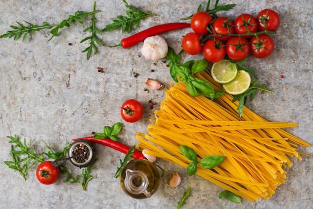 Паста тальятелле и ингредиенты для приготовления пищи (помидоры, чеснок, базилик, перец чили). вид сверху