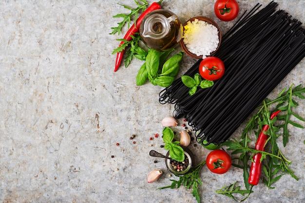 黒リングイネパスタの材料-トマト、バジル、チリ。上面図