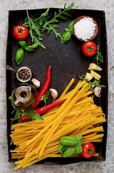 パスタタリアテッレと料理の材料(トマト、ニンニク、バジル、チリ)。上面図
