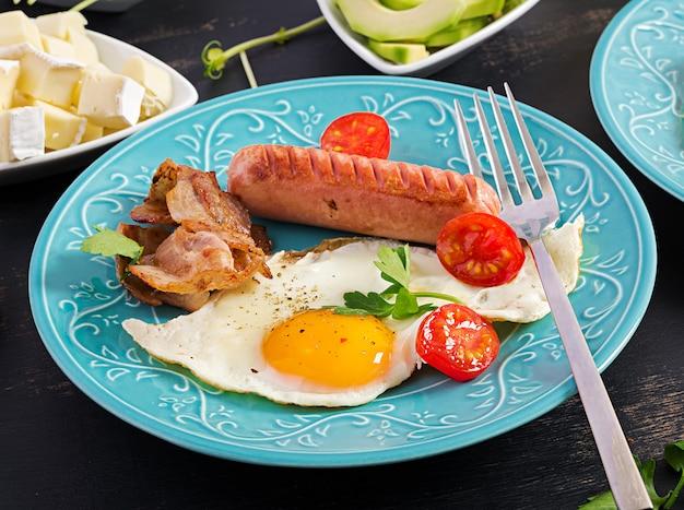 イングリッシュブレックファースト-目玉焼き、トマト、ソーセージ、ベーコン。