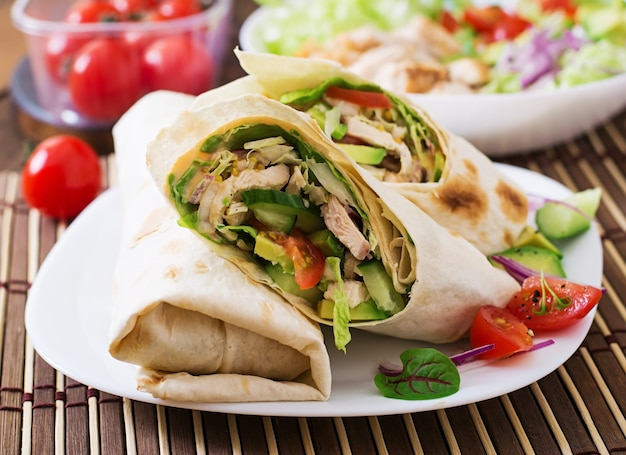 Свежие тортилья обертывания с курицей и свежими овощами на тарелке