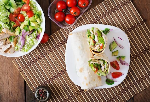Свежие тортилья обертывания с курицей и свежие овощи на тарелку. вид сверху