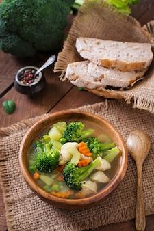 ブロッコリー、グリーンピース、ニンジン、セロリのボウルにチキンスープ