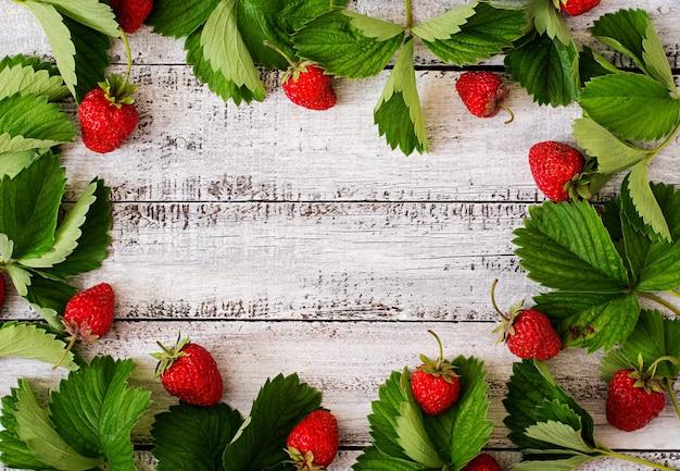 木製の背景に熟したイチゴと葉のフレーム。上面図