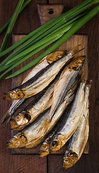 Копченая килька и зеленый лук на разделочную доску. копченая рыба. вид сверху