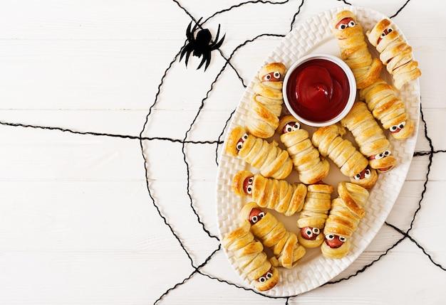 テーブルに面白い目をした生地で怖いソーセージミイラ。面白い装飾。ハロウィーン料理。上面図。平置き