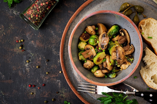 Веганское блюдо. запеченные грибы с брюссельской капустой и зеленью. правильное питание .. вид сверху