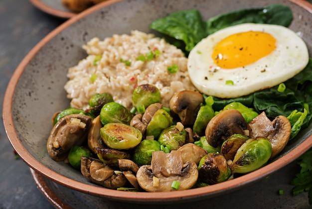 Здоровый завтрак. овсяная каша, яйцо и салат из запеченных овощей - грибов и брюссельской капусты.