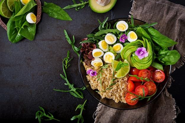 新鮮な野菜のヘルシーサラダ-トマト、アボカド、ルッコラ、卵、ほうれん草、キノアのボウル。平干し。上面図。